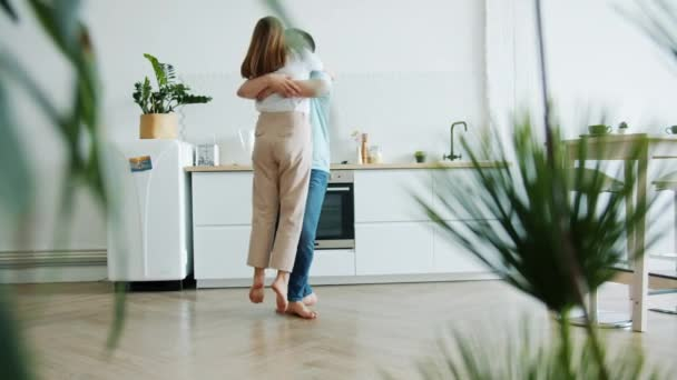 Happy millennials dancing in kitchen hugging having fun at home together