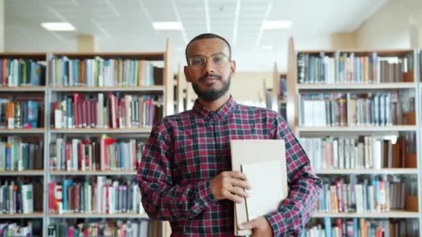 Portrét afrického amerického studenta chůze v univerzitní knihovně s knihami