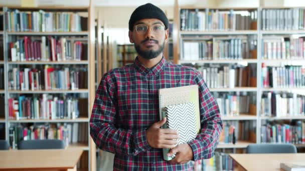 Portrait of serious African American student holding books in university library