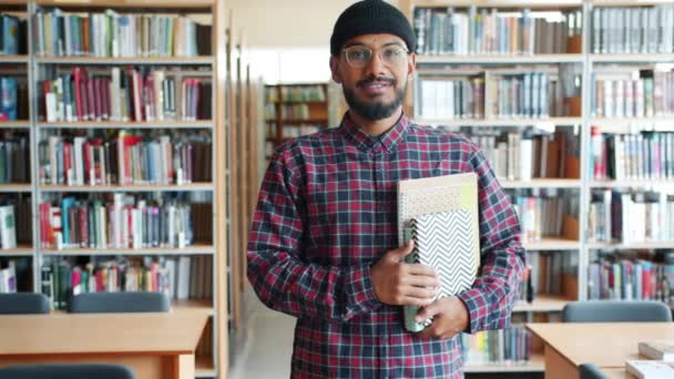 Slow motion of cheerful African American adult student holding books in library