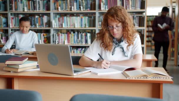 Chytrá holka dělá domácí úkoly v knihovně zatímco ostatní studenti studující