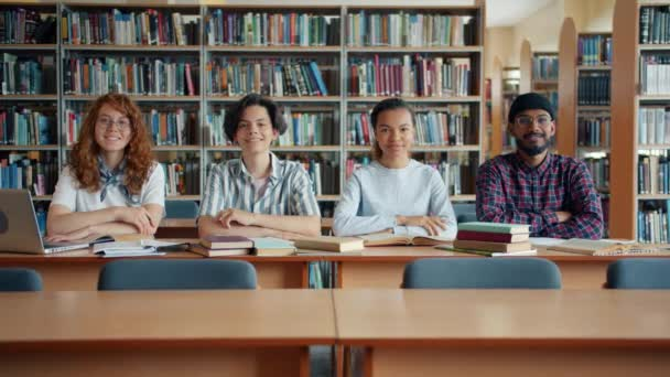 Multi-ethnic group of young people students sitting at desk in library smiling