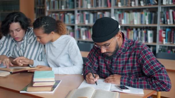 Multi-rasová skupina studentů studujících v knihovně psaní čtení knih mluvení