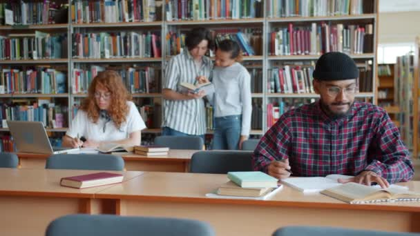 University students working in library reading books using laptop chatting