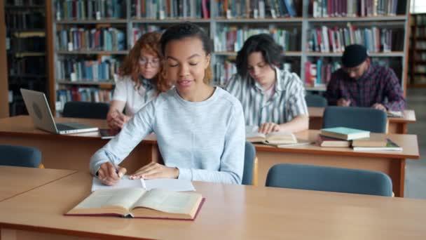 Africká americká dívka studující v knihovně čtení knih od studentského studenta