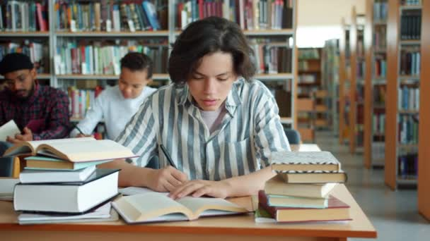 Slow motion of tired boy studying in college library reading book at desk