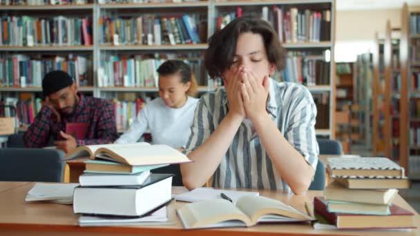 Vyčerpaná teenagera, který se učil v univerzitní knihovně u stolu