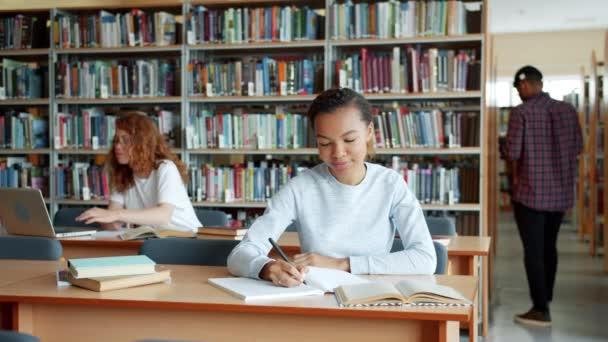 Skupina mladých lidí a dívek studujících v univerzitní knihovně pomocí knih