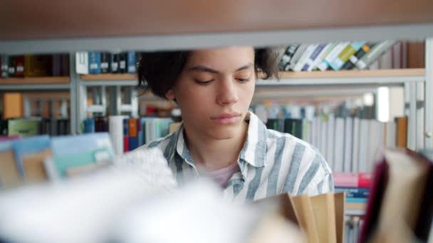 Portrét veselého teenagera, který si vybírá knihy ve střední knihovně s úsměvem