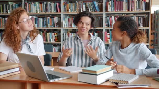 Pomalý pohyb šťastných studentů studujících v knihovně, jak se směje s vysokým pěti