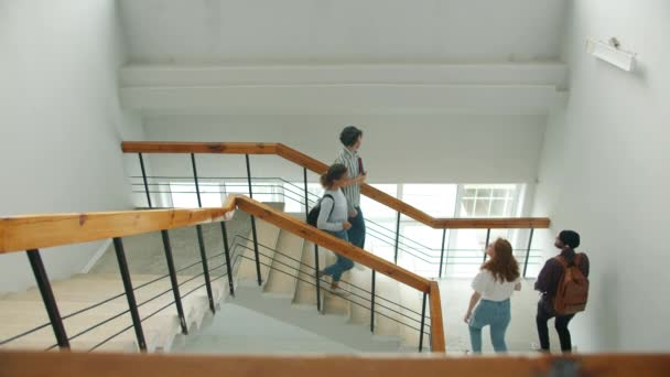 Multi-racial group of students meeting on stairs in college doing high-five