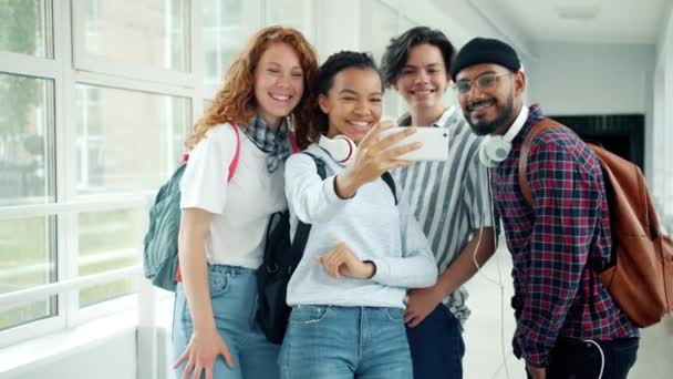 Multi-ethnic group of students taking selfie with smartphone in high school