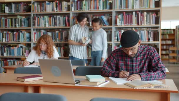 Pomalý pohyb mladých lidí v univerzitní knihovně studující mluvení čtení knih
