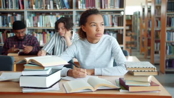 Unavená Afroameričanka studující v univerzitní knihovně psaní knih