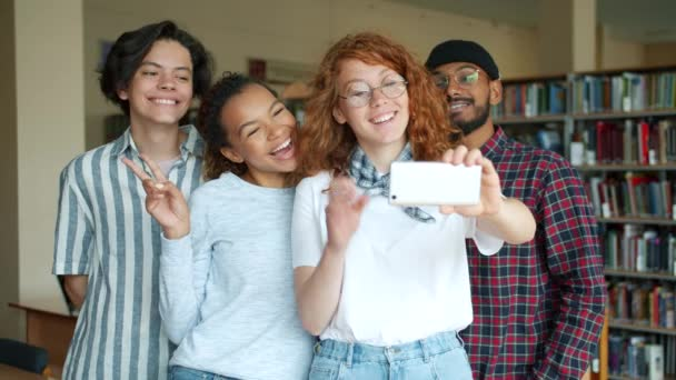 Portrait of happy students taking selfie in library with smartphone camera