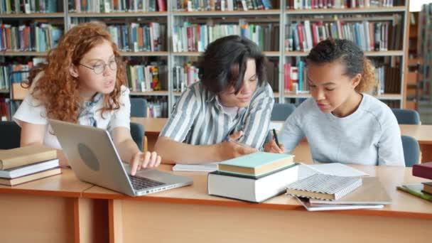 Csoport tizenévesek tanul az iskolai könyvtár laptop és könyvek beszél