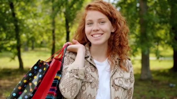 Portrét veselého teenagera s papírovými sáčky stojící venku v parku s úsměvem