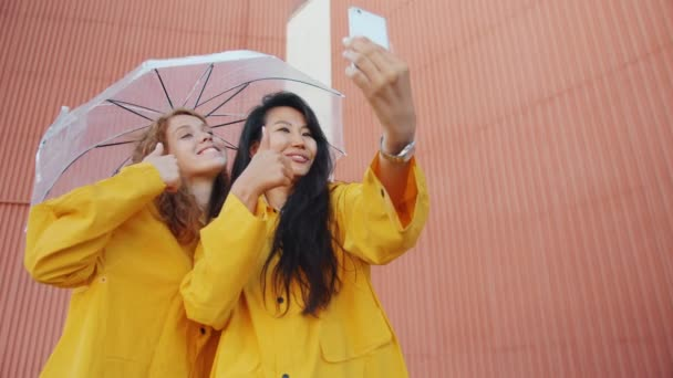 Girls taking selfie outdoors with smartphone holding umbrella wearing raincoats