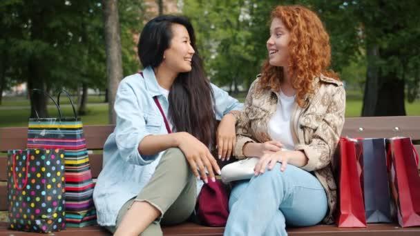 Lassú mozgás örömteli tinédzserek beszélgetni padon a parkban bevásárló táskák
