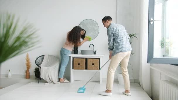 Fiatal férfi és nő takarítás fürdőszoba mosás tükör felmosó padló otthon