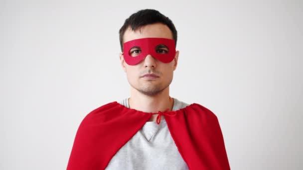 Egy Superman jelmezes fiatalember portréja piros maszkban és köpenyben, ahogy a kamerába néz.