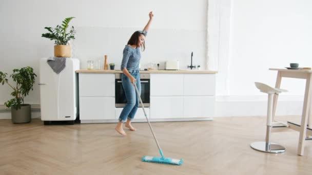 Šťastná mladá žena mytí podlahy s mop a tanec doma v kuchyni