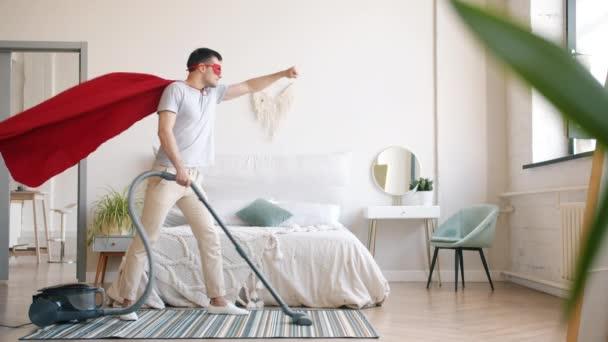 Guy v superman kostým čištění koberec s vysavačem v ložnici doma