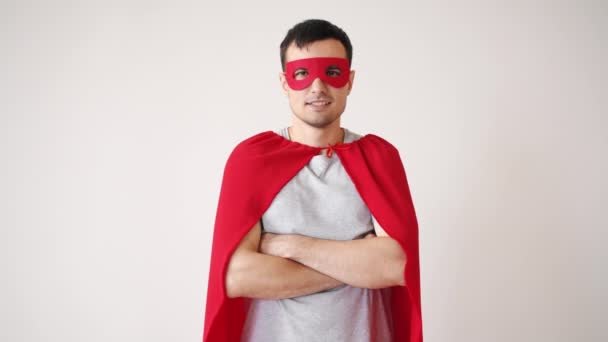 Portrait of smiling guy in superman costume standing with arms crossed alone