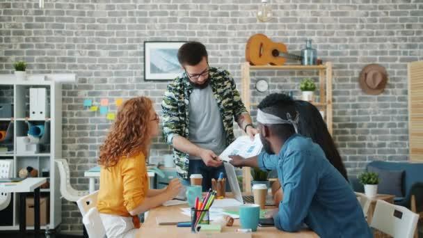 Anwendungsdesigner und -designerinnen diskutieren im Büro über Arbeit mit Diagrammen