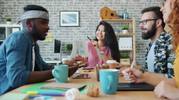Lányok és fiúk irodai dolgozók megvitatása smartphone alkalmazás tervezése a munkahelyen
