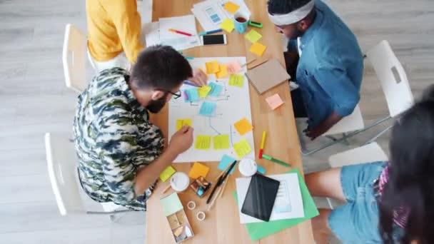 Kreatív emberek csoportja rohan az asztalhoz, hogy együtt dolgozzanak a projektben.