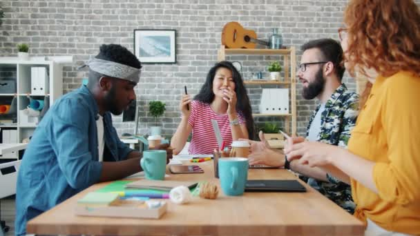 Multi-racial group of coworkers talking working in office discussing business