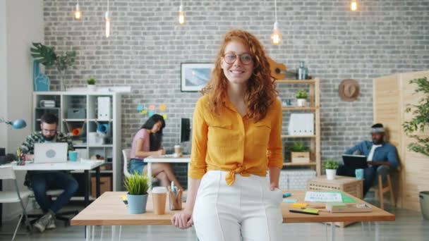 Slow motion of pretty smiling girl standing in office looking at camera