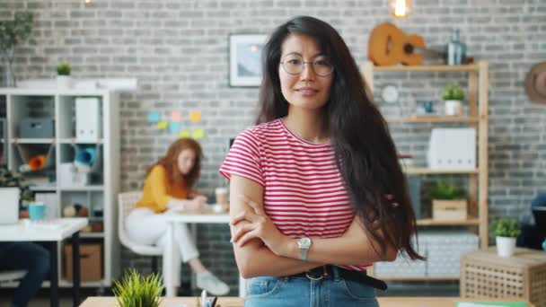 Portrait of attractive Asian lady standing indoors in office with arms crossed