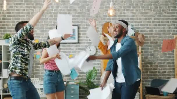 Happy young men and ladies dancing in office throwing business papers laughing