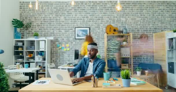 Time-lapse of African American man working with modern laptop in office