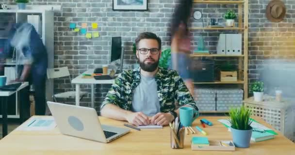 Zoom-out time lapse of attractive guy with serious face working in office