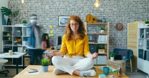 Zoom-in time lapse of pretty girl meditating on desk in office enjoying break
