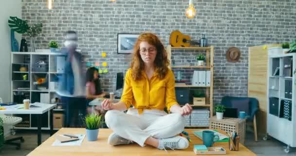 Time-laps of female employee enjoying work break sitting in lotus pose on desk
