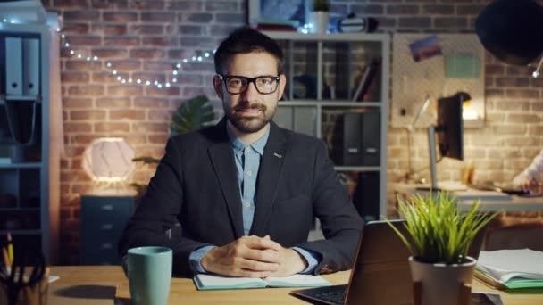 Zeitlupe Porträt eines hübschen Kerls Büroangestellte lächelt in dunklen Arbeitsplatz