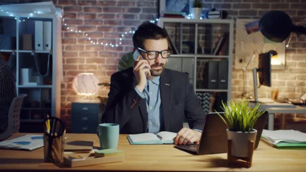 Cheerful guy chatting on mobile phone in office in the evening discussing work