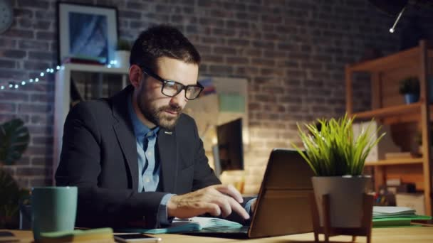 Specialist young man using laptop in dark office smiling feeling happy at work