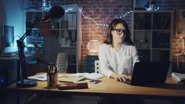 Porträt einer Frau, die Kollegin im Büro um Hilfe bei Computergesprächen bittet