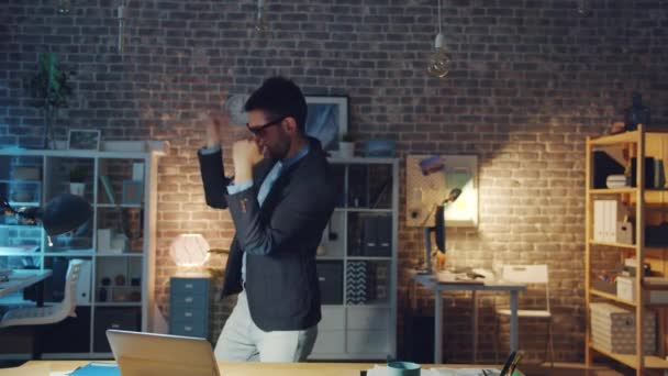 Slow motion of happy young man dancing in office wearing funny glasses