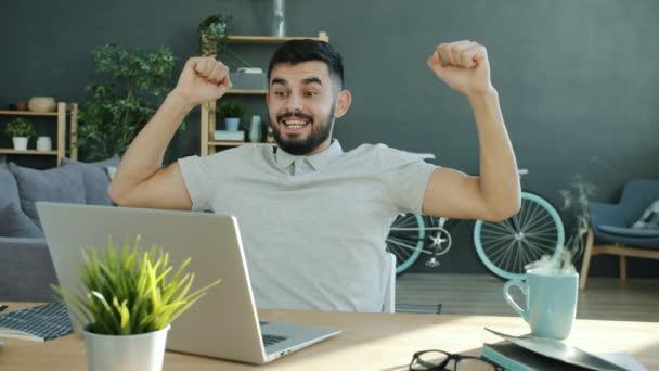Cinemagraph-Schleife aufgeregter Freelancer mit guten Nachrichten beim Blick auf den heimischen Laptop-Bildschirm