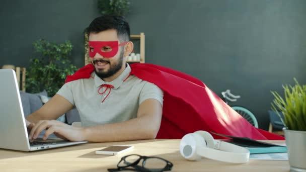 Portré a fiatal férfi szuperhős jelmezben dolgozik laptop a lakásban
