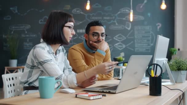 Tvůrčí mladí lidé žena a muž sdílení nápadů mluvit pomocí notebooku v kanceláři