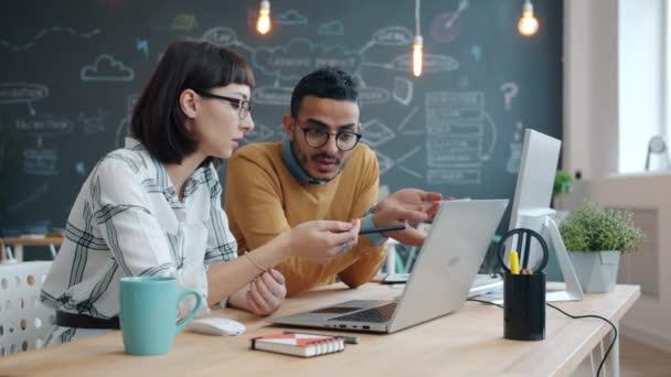 Zpomalený pohyb smíšených závodních spolupracovníků mluvících v kanceláři při pohledu na obrazovku notebooku