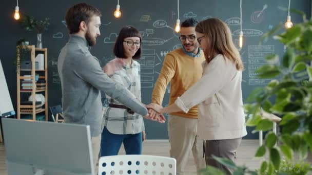 Multi-ethnic business team joining hands in office expressing cooperation then laughing