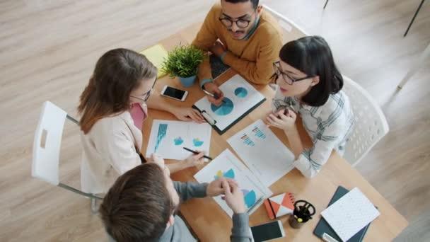 Vysoký úhel pohledu mladých lidí kolegů diskutujících o projektu při pohledu na grafy v úřadu